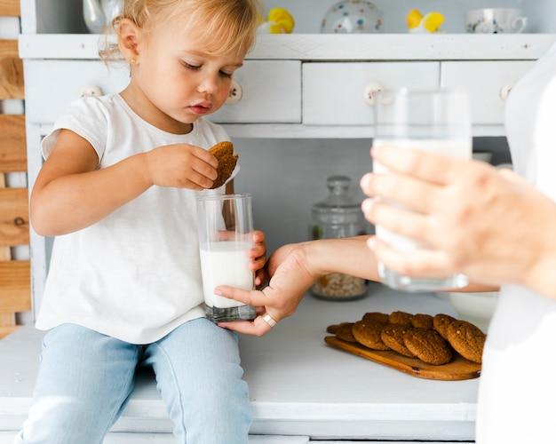 クッキーとミルクを食べる愛らしい娘 無料写真