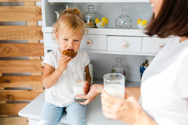 母は牛乳を飲むと娘がクッキーを食べる 無料写真