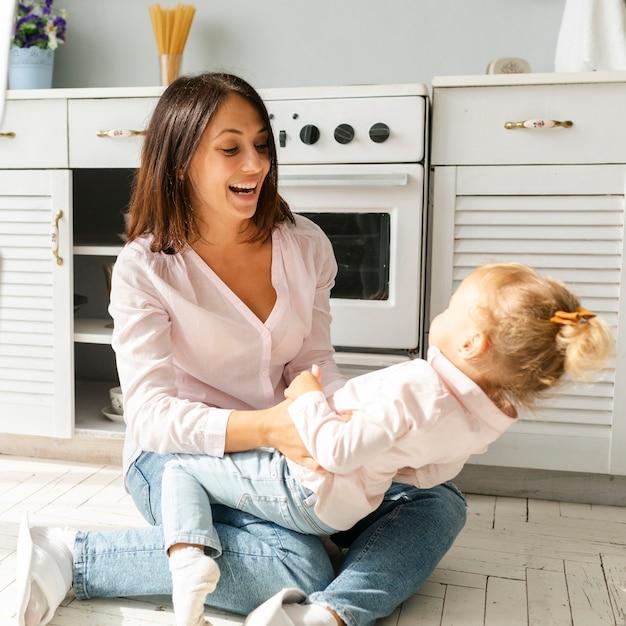 Мать и дочь, сидя на полу на кухне Бесплатные Фотографии