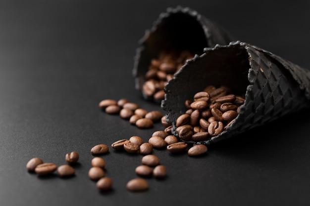 暗いテーブルの上のコーヒー豆と暗いコーン 無料写真