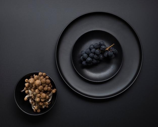 黒の背景にブドウと暗いプレート 無料写真
