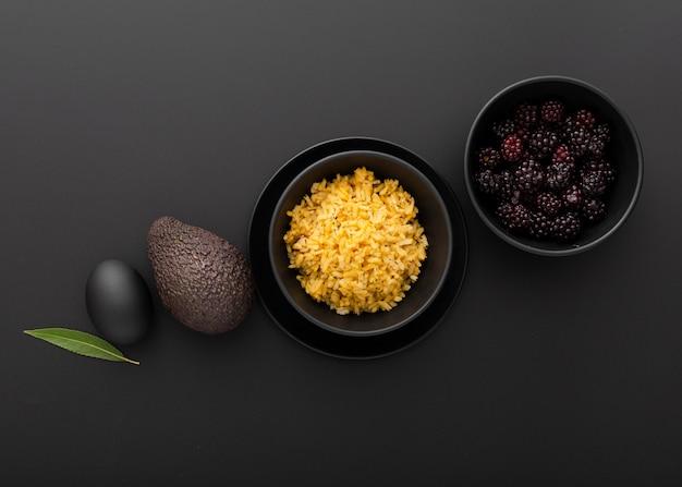 Темные чаши с рисом и авокадо на темном столе Бесплатные Фотографии