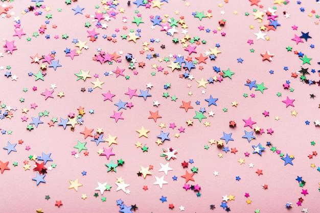 ピンクの背景にカラフルな紙吹雪星 無料写真