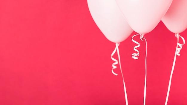 コピースペースと赤の背景にピンクの風船 無料写真