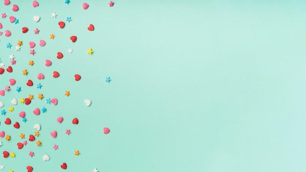 Звезды и сердца конфетти на бирюзовом фоне с копией пространства Бесплатные Фотографии