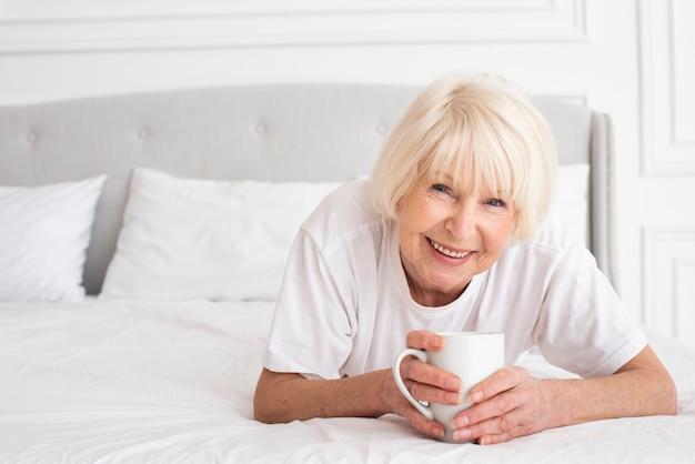 Счастливая старшая женщина держит чашку Бесплатные Фотографии