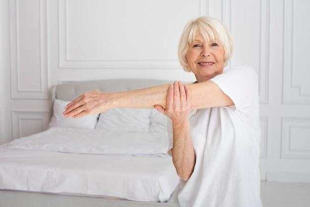 寝室でスポーツをしている年配の女性 無料写真