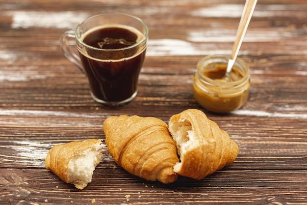 Круассаны с чашкой кофе и арахисовым маслом на столе Бесплатные Фотографии