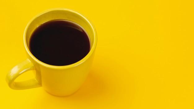 黄色の背景に黄色のコーヒーカップ 無料写真