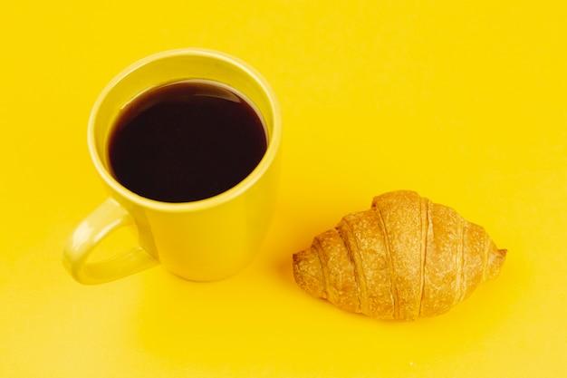 Желтая чашка с кофе и круассаном на желтом фоне Бесплатные Фотографии