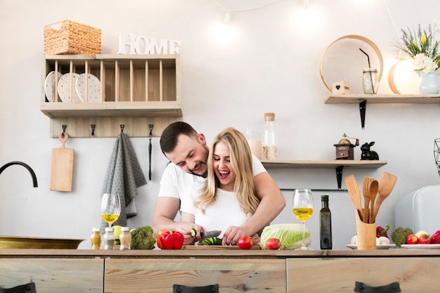 Счастливая молодая пара, приготовление пищи вместе Бесплатные Фотографии