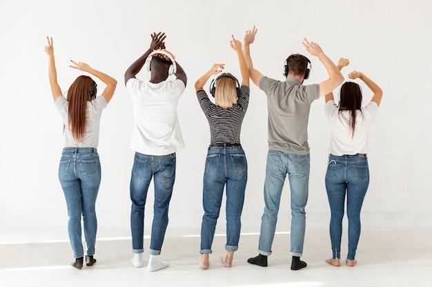 ヘッドフォンを持つ人々のグループは背中を向けた 無料写真