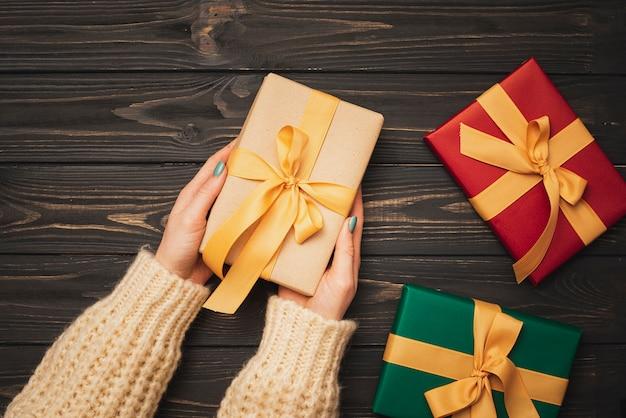 ゴールデンリボンとクリスマスプレゼントを両手 無料写真