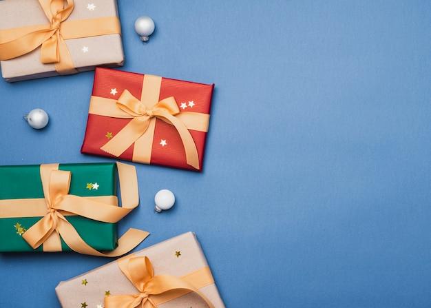 青の背景にリボンでカラフルなプレゼント 無料写真