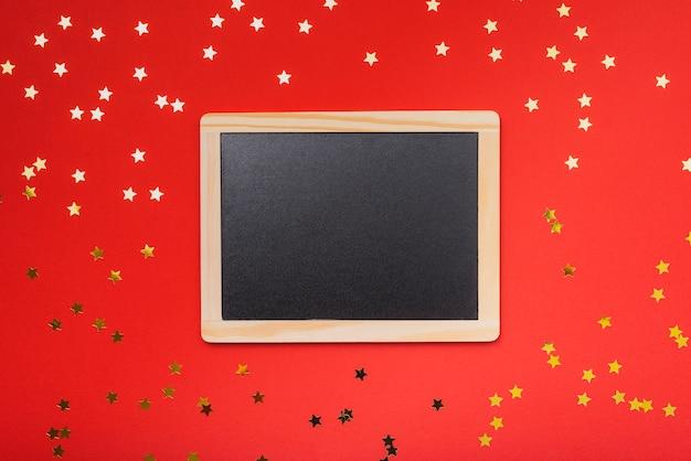赤い背景と金色の星と黒板のモックアップ 無料写真