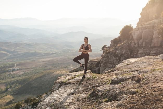 Вид спереди молодая женщина медитирует Бесплатные Фотографии