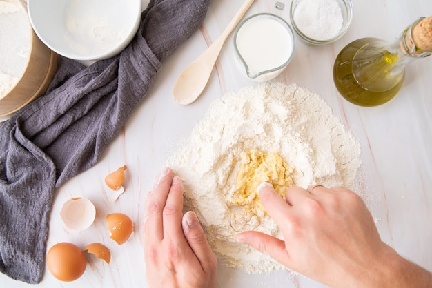 Вид сверху шеф-повар смешивания яиц с мукой Бесплатные Фотографии