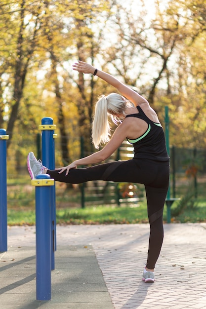 Вид сзади женщина делает упражнения на растяжку Бесплатные Фотографии