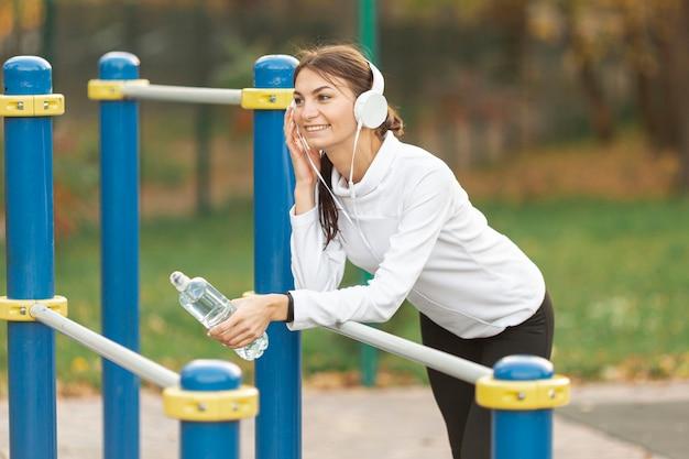 音楽を聴くと水のボトルを保持している笑顔の女性 無料写真