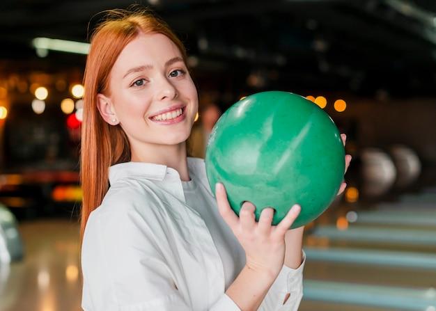 ボウリングのボールを保持している赤毛の女性 無料写真
