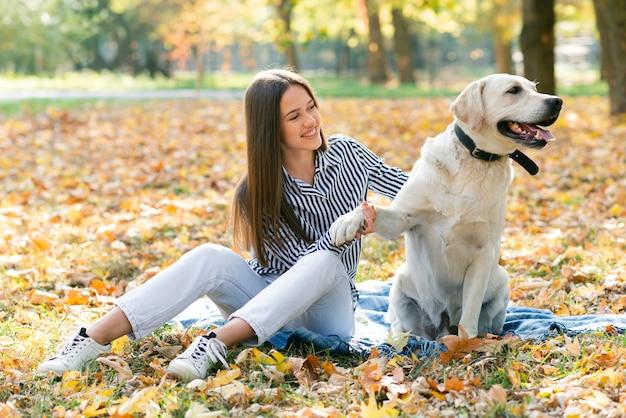 Взрослая женщина играет со своей собакой в парке Бесплатные Фотографии