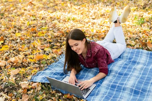 公園の毛布の上に座っている若い女性 無料写真