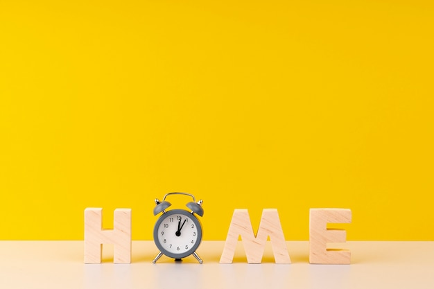 Домашняя надпись с деревянными буквами и часами на желтом фоне Бесплатные Фотографии