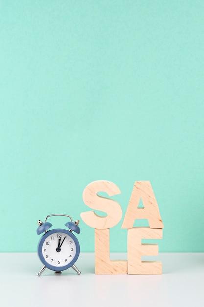 青色の背景に時計の横にある木製の販売レタリング 無料写真
