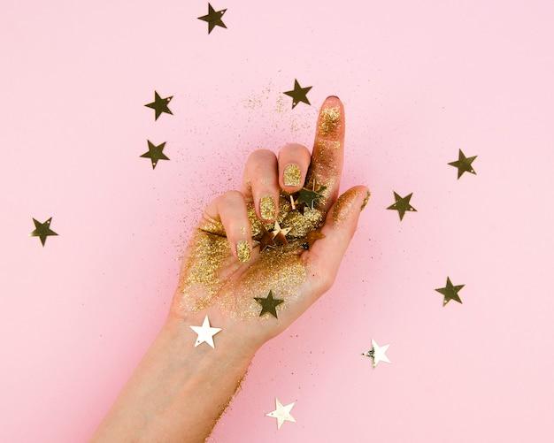 Макро рука с золотыми звездами Бесплатные Фотографии