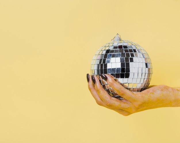 クリスマスボールの正面を持っている手 無料写真