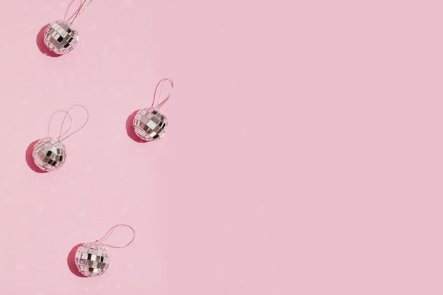 コピースペースとピンクの背景に銀のクリスマスボール 無料写真
