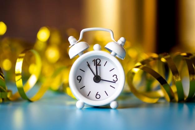 リボンゴールデン背景に正面白い時計 無料写真