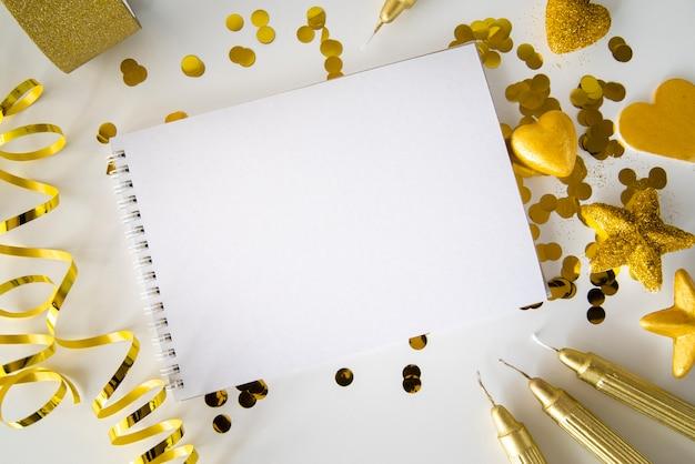ゴールデンリボンとスパンコールに囲まれた空のメモ帳のトップビュー 無料写真