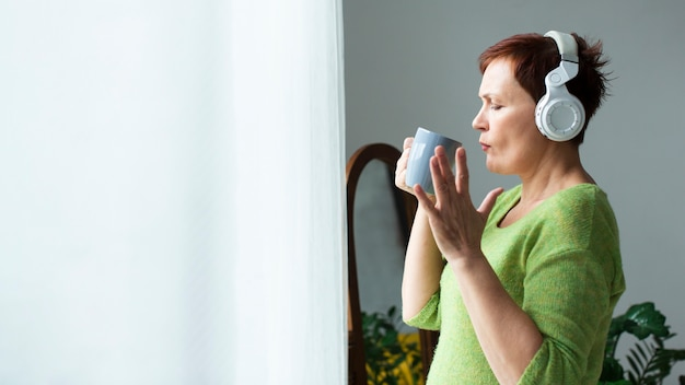 音楽を聴くとマグカップを保持している側面図女性 無料写真