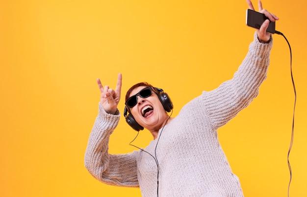 ロック音楽を聴いて幸せな年配の女性 無料写真