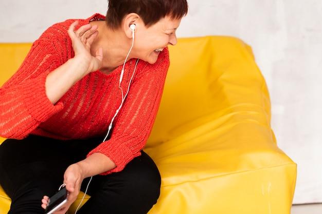 ソファの上に立地し、音楽を聴く女性 無料写真