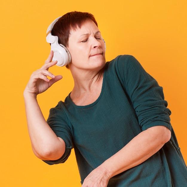 ミディアムショットの年配の女性のダンスと音楽を聴く 無料写真