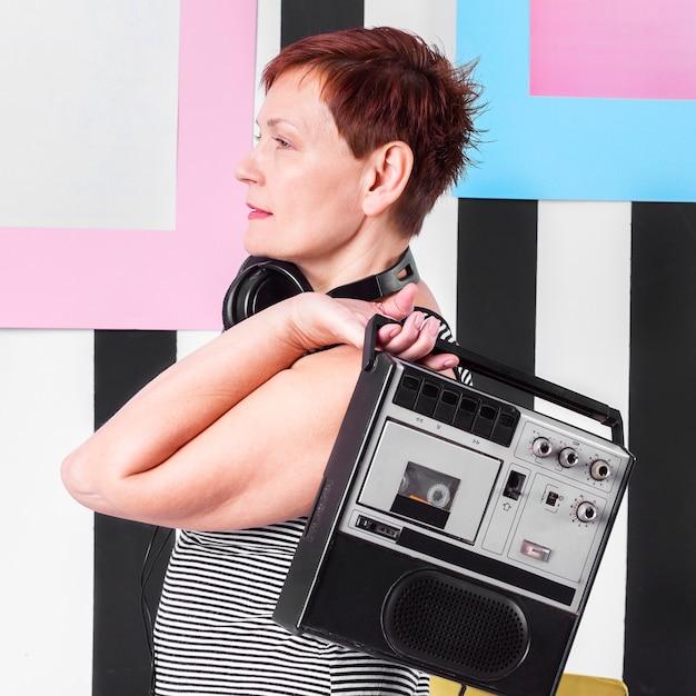 ビンテージカセットプレーヤーを保持している年配の女性の肖像画 無料写真