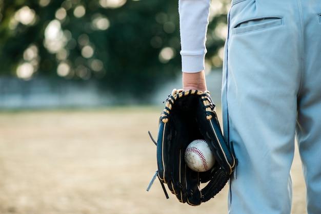 Вид сзади мужчина держит бейсбол в перчатке Бесплатные Фотографии