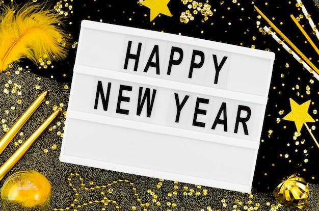 Новогодняя надпись на белой карточке с золотыми аксессуарами Бесплатные Фотографии