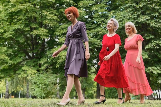 公園を歩いているエレガントな年配の女性 無料写真