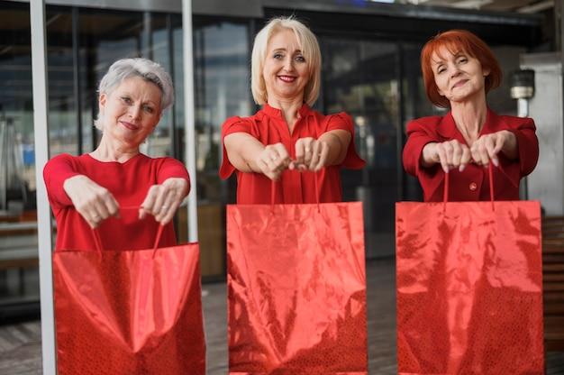 買い物袋を保持している幸せな年配の女性 無料写真
