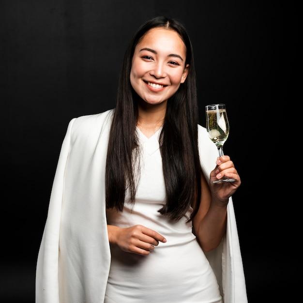シャンパンのグラスを保持しているスタイリッシュな女性 無料写真
