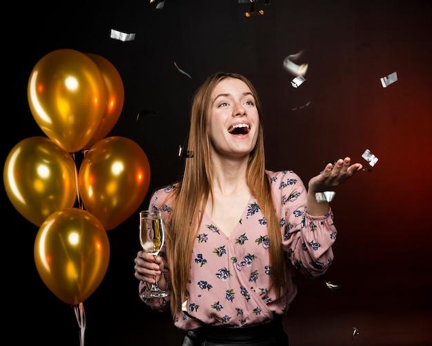 幸せであり、黄金の風船でガラスを保持している女性 無料写真