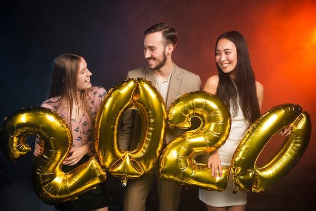 Средний снимок друзей с воздушными шарами на новогодней вечеринке Бесплатные Фотографии