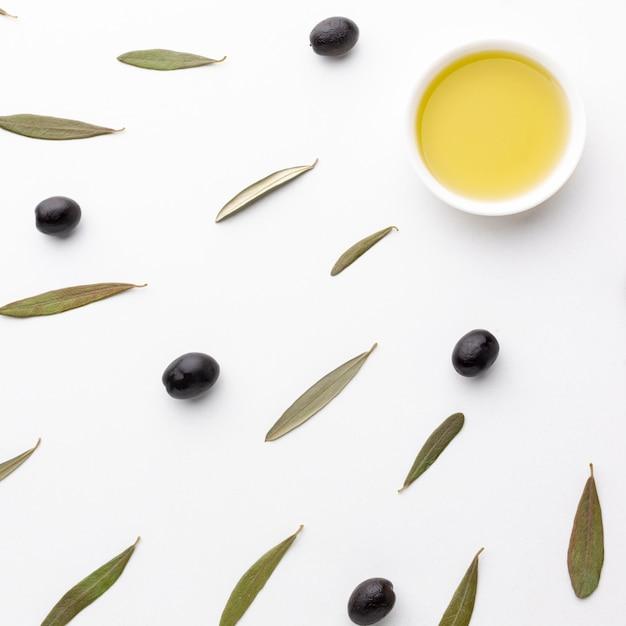 ソーサーにオリーブオイルと葉と黒オリーブ 無料写真