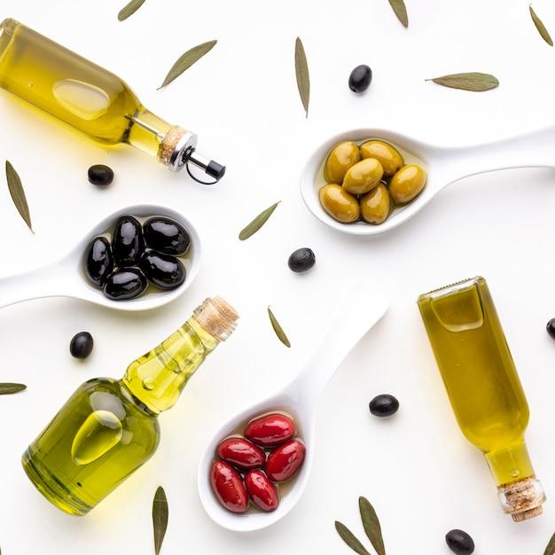 Вид сверху желтые красные маслины в ложках с листьями и масляными бутылками Бесплатные Фотографии