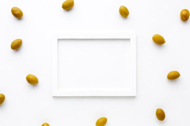 白いフレームのモックアップと黄色のオリーブ 無料写真