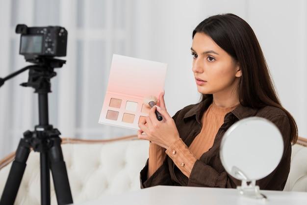 カメラで彼女の化粧をしている若い女性 無料写真