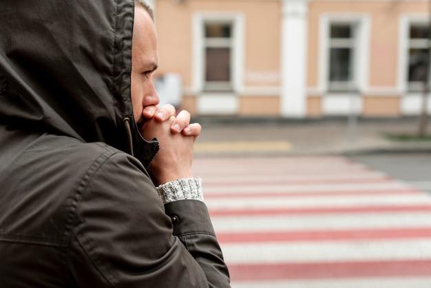 彼の手を温めようとしている男の肖像 無料写真